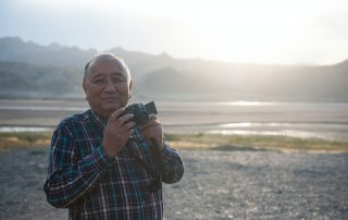 A man holding a camera - 10 hobbies to take up in retirement.